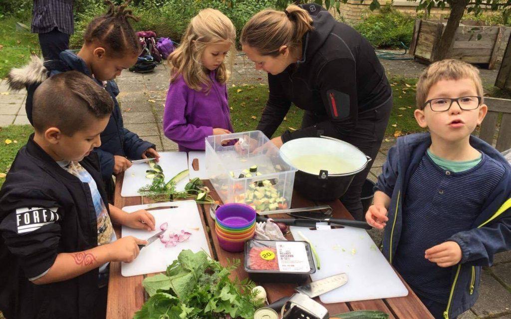 Børn Fra Hareskovskolen laver mad i udekøkken på Demenscenter Bakkegården. Foto: Ulla Skovsbøl